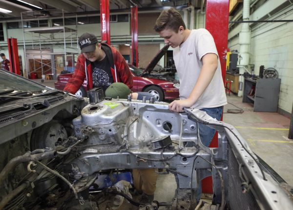 Two Teenagers work on car engine